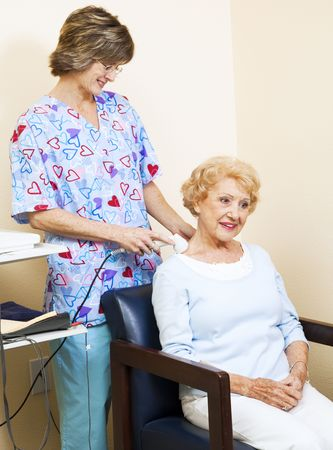 Physical therapist uses ultrasound to relief chiropractic patients neck pain.   photo