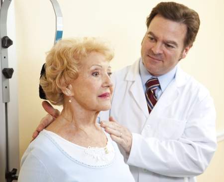 physical therapy: Senior woman exercising her neck with the help of a chiropractor.