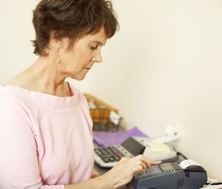 Store clerk types information into a credit card scanning machine.   Stock Photo - 7367249