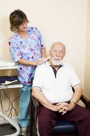 Senior man gets ultrasound therapy for his neck pain.   photo