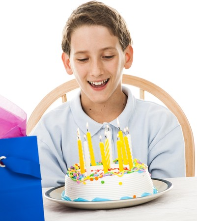 Adorable little boy gets ready to blow out the candles on his birthday cake.  White background. Stock Photo - 7433415