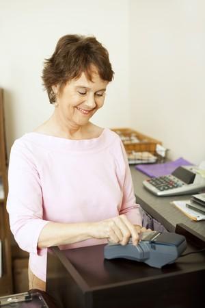 Store clerk runs a customer's credit card through the terminal. Stock Photo - 7433385