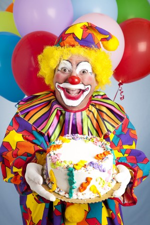 Crazy clown with balloons, holding a birthday cake.   photo