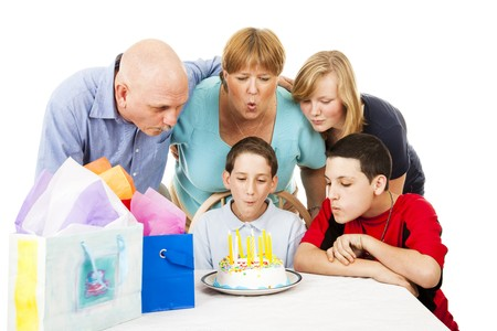 birthday party kids: Family helps a little boy blow out his birthday candles.  White background. Stock Photo