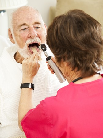 depressor: Home healthcare nurse uses a tongue depressor and otoscope to look inside an elderly patients mouth.
