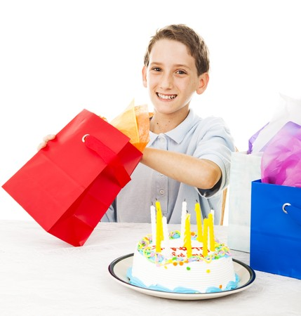 Cute little boy opening a birthday gift.  White background. photo