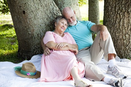 Beautiful senior couple relaxes in the shade at the park.   photo