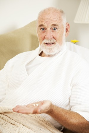 Senior man sick in bed doesnt want to take his medicine.   photo