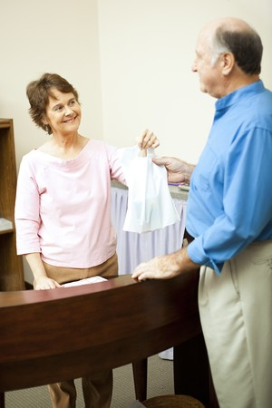 Store clerk hands a customer's purchases to him in a bag. Stock Photo - 7433358