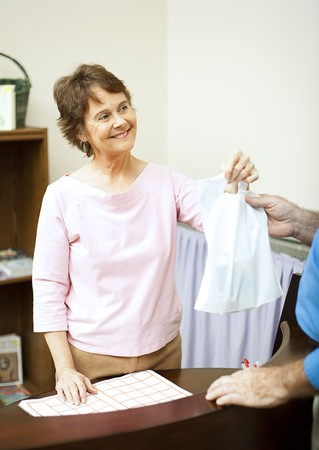 Store clerk hands a plastic bag to customer. Stock Photo - 7475459