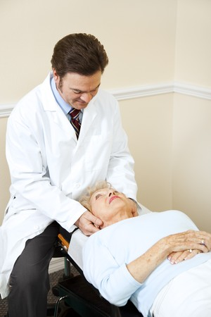 Senior woman gets her neck adjusted by a caring chiropractor.   photo