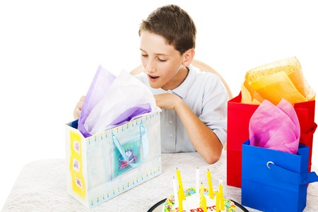 Cute little boy opening his birthday presents.  White background. photo