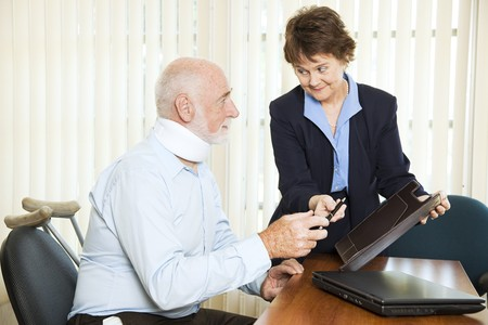 Injured man signing a settlement offer from the attorney.   photo