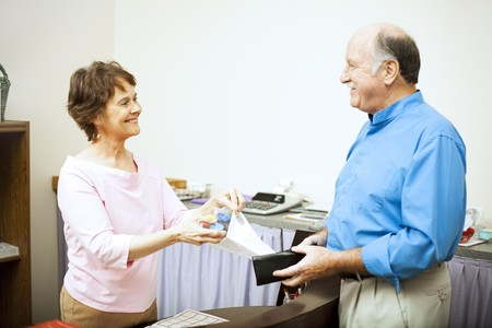 Sales clerk bags up a purchase for a customer.   Stock Photo - 7475456