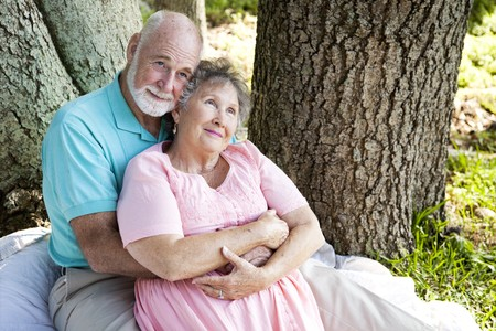 Nostalgic senior couple sitting outdoors and remembering.   photo