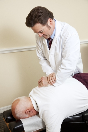 Senior man gets an adjustment to a friendly chiropractor.   photo