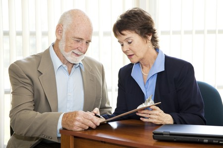 signing a contract: Senior man signing a contract in his attorneys office.   Stock Photo