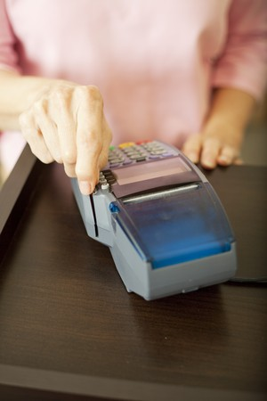 Closeup of a woman's had swiping a debit card through a scanner.  Shallow depth of field.   Stock Photo - 7477751