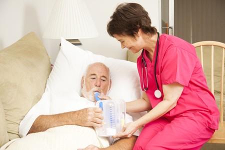 Enfermera de salud en el hogar ayuda a un paciente senior con su terapia respiratoria.