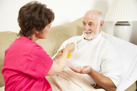 Home health nurse giving an elderly patient juice to make his medicine go down.   Stockfoto