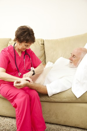 Home health nurse taking an elderly patients pulse.   photo