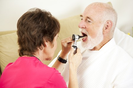 otoscope: Home health nurse checks a patients throat with an otoscope.