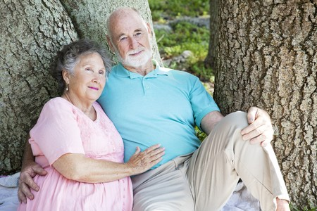 sitting on the ground: Senior couple relaxing together in the park under a tree.