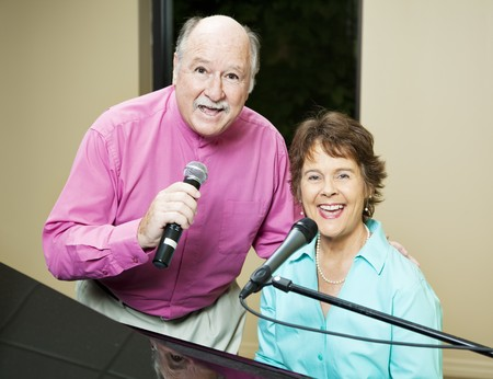 Talented senior couple sings and plays piano.   photo