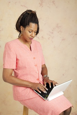 cornrows: Businesswoman uses a tiny netbook computer to access the internet.