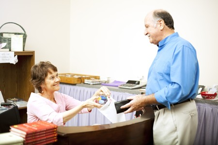 Store clerk in a wheelchair bags a customer's purchase.  Room for text. Stock Photo - 7627359