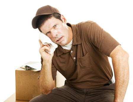 Exhausted delivery guy takes a break.  Isolated on white.   photo