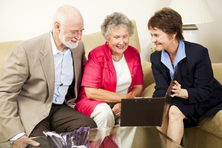 property agent: Saleswoman meets with senior couple in their home.  Could be real estate, life insurance, etc.