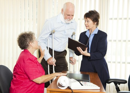 neck injury: Injured man and his wife meet with a personal injury lawyer.