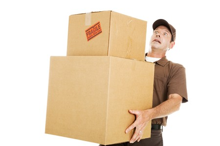 Delivery man or mover about to drop a stack of large boxes.  Isolated on white.   版權商用圖片
