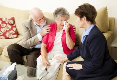Senior pareja ve un terapeuta para sobrellevar el dolor. Podría también ser director del funeral reunión con clientes.