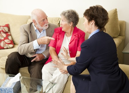 psychotherapy: Senior couple in therapy, working out their problems with a counselor.