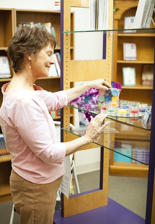 Bookstore owner arranges a display in her shop.   Stock Photo - 7627369