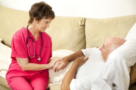 companion: Compassionate home health nurse holds an elderly patients hand.