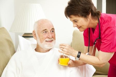 Home nurse giving her elderly patient a glass of orange juice.   photo