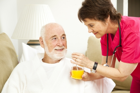 home health care: Home nurse giving her elderly patient a glass of orange juice.   Stock Photo