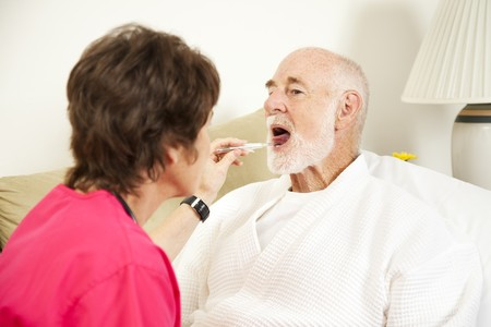 Home nurse uses a thermometer to take an elderly patients temperature.   photo