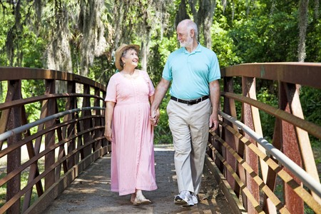 Beautiful senior coule stays fit by walking together in the park.   photo