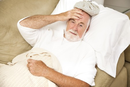 Senior man home sick in bed, with an ice pack on his head.  Could be hangover or illness. photo