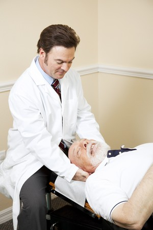 Chiropractor treats a senior man for neck pain.   photo