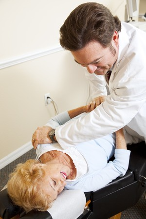 Senior woman gets relief from back pain when her chiropractor adjusts her spine.   photo