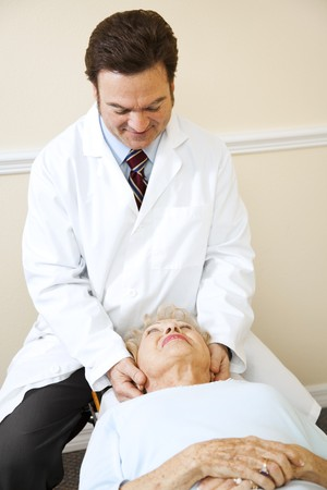 Friendly chiropractor adjusts a senior womans cervical spine (neck). photo