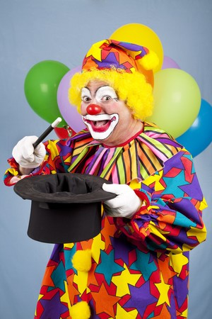 Funny birthday clown does magic tricks with a top hat and wand.   photo