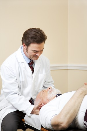 Chiropractor adjusts the neck of a senior male patient.   photo