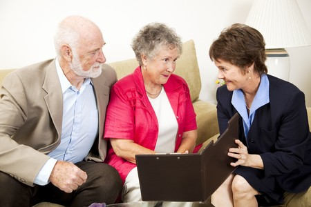Senior couple listens to a sales pitch in their home.   photo