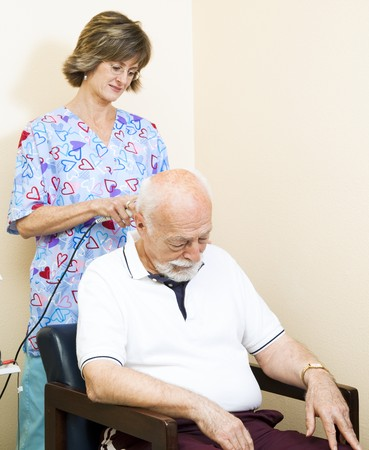 Senior man getting ultrasound therapy on his neck, at the chiropractors office.   photo